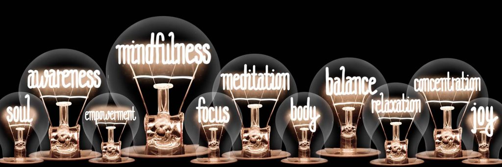 Group of light bulbs with shining fibers in a shape of Mindfulness, Meditation, Balance, Awarness, Body and Soul concept related words isolated on black background.